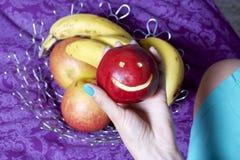 Una mujer toma una manzana roja con un emoticon tallado de un plato Hay una cesta de fruta en el fondo Varias manzanas y plátano fotografía de archivo libre de regalías