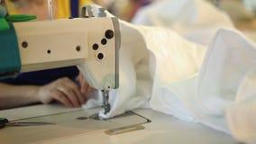 Una mujer trabaja en una fábrica de costura, adaptación, modistería, máquina de coser, costura de cubiertas almacen de metraje de vídeo