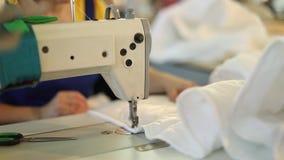 Una mujer trabaja en una fábrica de costura, adaptación, modistería, máquina de coser, costura de cubiertas metrajes