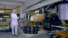 Una mujer trabaja en una planta de comida, mecanografiando en una máquina cerca de un transportador con los microprocesadores almacen de video