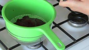 Una mujer transfiere los arándanos cocinados con el azúcar de un cazo en un colador Prepara los pur?s de patata para la melcocha almacen de video