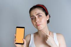 Una mujer trastornada joven que lleva a cabo un smartphone y puntos su finger en las espinillas en su cara El concepto de cosmeto fotos de archivo libres de regalías