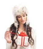 Una mujer triguena joven que abre un regalo de Navidad Fotografía de archivo