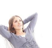 Una mujer triguena joven que se relaja en un sofá blanco Imágenes de archivo libres de regalías
