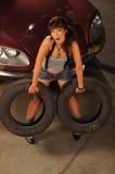 Una mujer triguena joven que sostiene los neumáticos de coche acerca a un coche Imagen de archivo