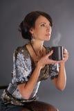 Una mujer triguena joven que sostiene una taza de café imagen de archivo