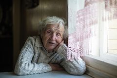 Una mujer triste mayor que se sienta en una tabla en la casa fotografía de archivo libre de regalías