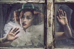Una mujer triste sola del pierrot detrás del vidrio imagen de archivo