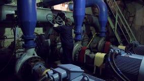 Una mujer tuerce la válvula industrial almacen de metraje de vídeo
