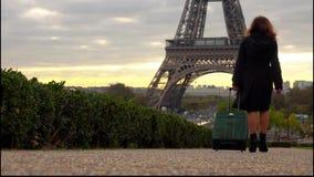 Una mujer turística con una maleta está caminando a la torre Eiffel almacen de video