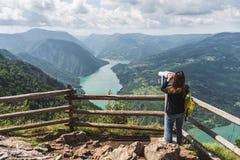Una mujer turística mira la naturaleza hermosa con un stationar Imágenes de archivo libres de regalías
