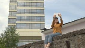 Una mujer utiliza una tableta al borde del tejado