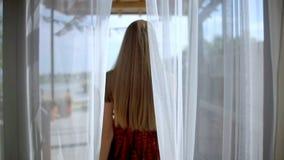 Una mujer va al paso al aire libre a través de las cortinas almacen de video