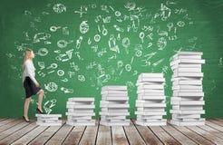 Una mujer va el consumir las escaleras que se hacen de los libros blancos Los iconos educativos se dibujan en la pizarra verde Fl Imagenes de archivo