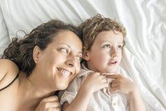 Una mujer y su hijo que juegan en cama imagenes de archivo