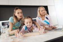 Una mujer y su madre están enseñando a su hija a cocinar las tortas hechas en casa La muchacha rueda la pasta con un rodillo Imagenes de archivo