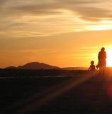 Una mujer y su niño en puesta del sol Foto de archivo