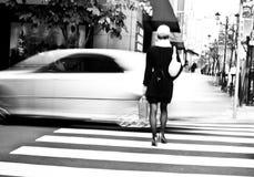 Una mujer y un coche en la falta de definición de movimiento Imagen de archivo libre de regalías