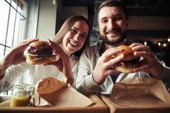 Una mujer y un hombre están gozando de sus hamburguesas Imagen de archivo libre de regalías