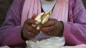 Una mujer y un maíz gigante en un mercado callejero en cuzco almacen de video