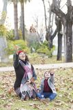 Una mujer y un niño que juegan con una hoja de la caída del otoño fotos de archivo libres de regalías