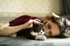 Una mujer y un pequeño gatito británico blanco y negro están mintiendo en el sofá fotografía de archivo
