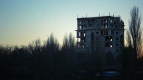 Una multitud de los cuervos que vuelan sobre las ruinas del edificio oscuridad Puesta del sol