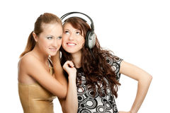 Una musica d'ascolto delle due belle ragazze Immagine Stock