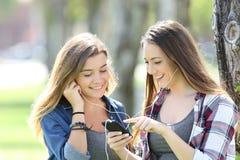 Una musica d'ascolto di due amici teenager felici Fotografie Stock Libere da Diritti