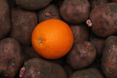 Una naranja hermosa en una patata vieja Imagenes de archivo