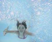 Una natación feliz de la niña en una piscina Imagen de archivo