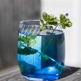 Una natura morta con liquido di vetro e blu Fotografia Stock
