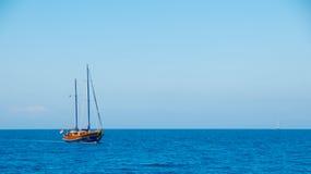 Una nave con las velas abajo en el horizonte de mar Foto de archivo libre de regalías
