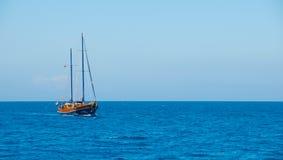 Una nave con las velas abajo en el horizonte de mar Fotos de archivo libres de regalías