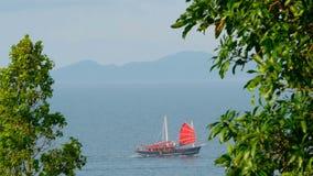 Una nave del cinese tradizionale con le vele rosse galleggia lungo il mare al tramonto archivi video