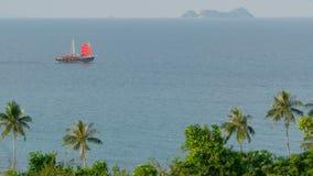 Una nave del cinese tradizionale con le vele rosse galleggia lungo il mare al tramonto stock footage