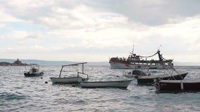 Una nave grande llenó de la gente que flotaba en el mar abierto y que mostraba a gente la costa de Makarska almacen de metraje de vídeo