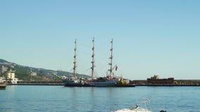 Una nave hermosa de la tres-navegación está navegando al puerto y es acompañada por dos barcos remolcadores en Yalta 4k almacen de metraje de vídeo