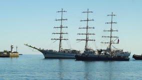Una nave hermosa de la tres-navegación está navegando al puerto y es acompañada por dos barcos remolcadores en Yalta 4k metrajes