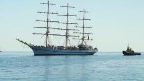 Una nave hermosa de la tres-navegación está navegando al puerto y es acompañada por dos barcos remolcadores en Yalta 4k almacen de video