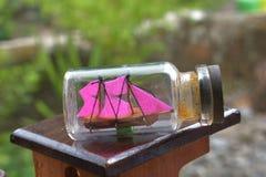 Una nave miniatura dentro de la botella en la foto muy cercana Foto de archivo