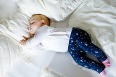 Una neonata adorabile sveglia di 6 mesi di sonno pacifico a letto Fotografia Stock