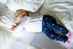Una neonata adorabile sveglia di 6 mesi di sonno pacifico a letto Immagini Stock