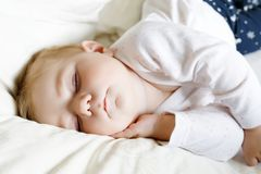 Una neonata adorabile sveglia di 6 mesi di sonno pacifico a letto Immagine Stock