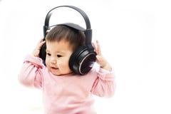 Una neonata ascolta musica con la cuffia con le mani Fotografia Stock Libera da Diritti