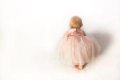Una neonata strisciante in abito da sera con tanti fronzoli rosa fotografia stock libera da diritti