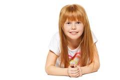 Una niña alegre con el pelo rojo está mintiendo; aislado en el blanco Fotografía de archivo