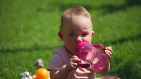 Una niña bebe el agua de una botella del plástico del ` s de los niños almacen de metraje de vídeo