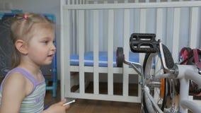 Una niña, bicicleta autorreparadora con un destornillador que se sienta en el cuarto de niños metrajes
