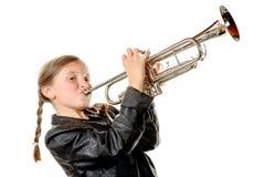 Una niña bonita con una chaqueta del negro toca la trompeta Imagenes de archivo